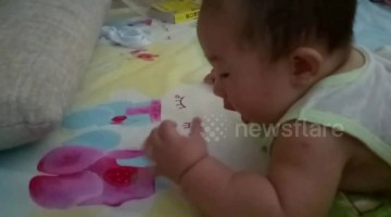 Cute baby tries to eat strawberry pattern on bed sheet