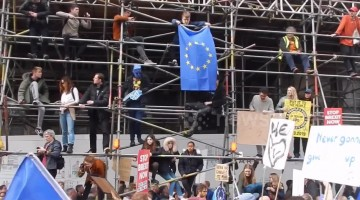Supporters for a People's Vote mount scaffolding and hold EU flag aloft