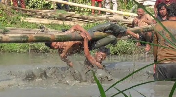 Contestants whack each other with bags of rice while balancing on pole over pool of mud in Indonesia