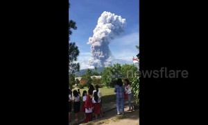 Schoolchildren watch as volcano erupts on quake-hit Indonesia island