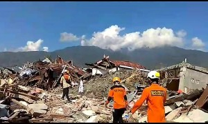 Rescuers walk through piles of rubble in aftermath of deadly Indonesia earthquake