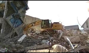 Excavator digs through debris from fallen hotel on earthquake-stricken Indonesia island