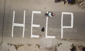 "Indonesians chalk large ""HELP"" on ground as authorities fear more than 5,000 still missing"