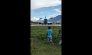 Cheeky boys knocked over by wind from jet plane