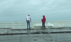 Two grown men play chicken with the tide in Aberystwyth