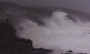 Huge swells and crashing waves in Cornwall as villagers look on