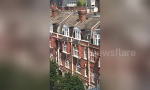 UK window cleaner seen on ledge three floors up with no safety equipment