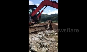 Skilled digger driver uses arm to fix broken machine