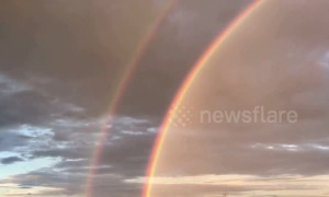 Beautiful double rainbow seen above Buddhist snake statue