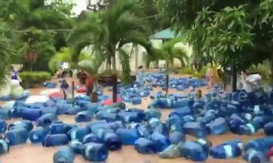 Hundreds of water dispensers float down flooded street after heavy downpour