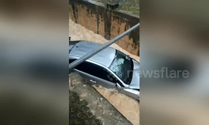 Car washed away after skidding into a storm drain flooded by Malaysian monsoon