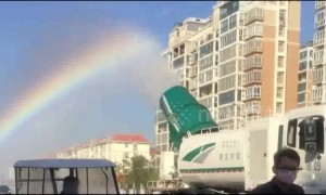 Lorry-mounted sprinkler leaves rainbow trail in the air behind it