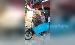 Easy drier! Moped rider keeps family out of rain with bizarre contraption