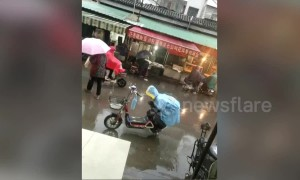Small boy keeps his mum's bike seat dry in the rain with his own body
