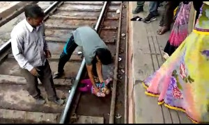 Moment miracle baby emerges unscathed after falling onto tracks and under moving train