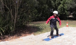 Australian science teacher gives daughter her first FlowRider experience using snowboard and shade cloth