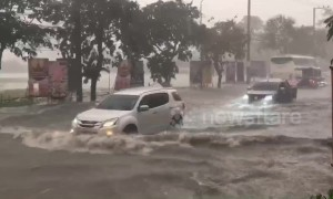 Cars drive through flooded streets of Pattaya, Thailand, as rainstorm hits