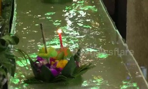 Worshippers send candle-lit baskets down a flume for Loy Krathong festival in Thailand