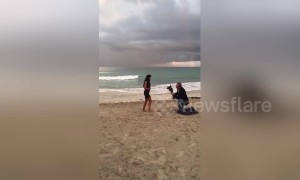 Boyfriend makes surprise beachside proposal under a rainbow