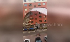 Woman freaks out when strong wind rips roof off building