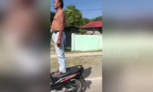 Drivers amazed by elderly man standing on moving motorcycle