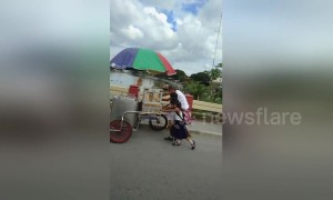 Tender moment schoolchildren help struggling elderly ice cream seller push cart up hill