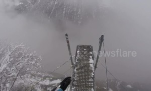 Man dives into the abyss wing-suiting through foggy Swiss valley
