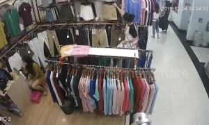 Thief steals clothes while shop assistant too busy doing her makeup to notice