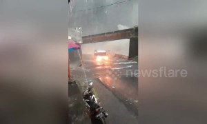 Bus drives through submerged highway during torrential floods in Indonesia