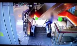 Naughty student climbs onto escalator handrail and falls one storey