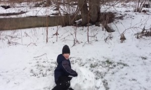 Boy Faces off with Big Snowball