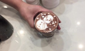 Skilled barista draws intricate snowman on hot chocolate drink