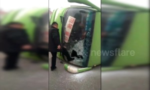 Car hits bus, flipping it over and trapping passengers inside