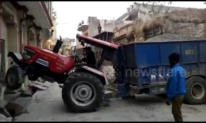 Whoops! Tractor driver gets stuck in between houses