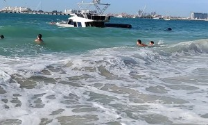 Onlookers Watch as Boat Sinks off the Coast of Dubai