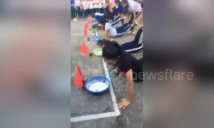 Girls in Vietnam engage in weird flour-eating wheelbarrow race