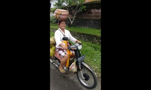 Motorcycling supermum in Bali carries groceries on her head and 4 gas cylinders