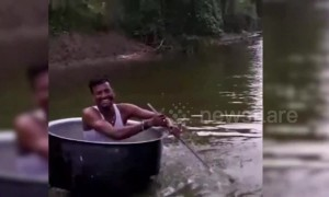 Man rows over water in cooking pot boat with spatula paddle