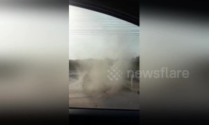 Terrified driver watches as dust devil approaches his car