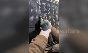 Skilful man shows off calligraphy on stone slab using a power grinder