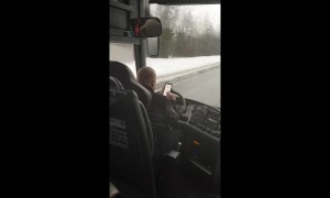 Bus driver types messages with both hands while driving on icy road