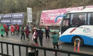 Stranded Chinese tourists get out of their bus and dance on icy motorway