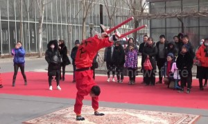 Performers impress visitors by somersaulting on stilts at Chinese temple fair