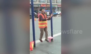 Old Chinese woman suspends her head from horizontal bar to work out