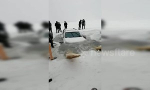 Family drifting car on frozen river end up breaking through thin ice