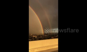 Spectacular double rainbow arcs over Los Angeles cityscape