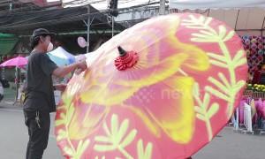 Graffiti artists spray paint contemporary designs on ancient Thai umbrellas