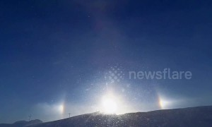 Sundog over snowy hilltop in Minnesota casts brilliant glare during blizzard