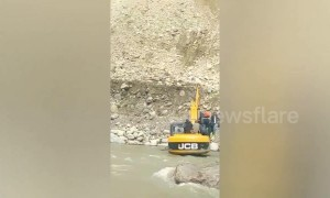 Local people transported by JCB across river to escape landslide in north India