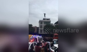 Alleged drunk man tight-rope walks on high voltage power lines